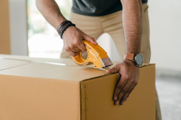 image of man taping cardboard box closed.